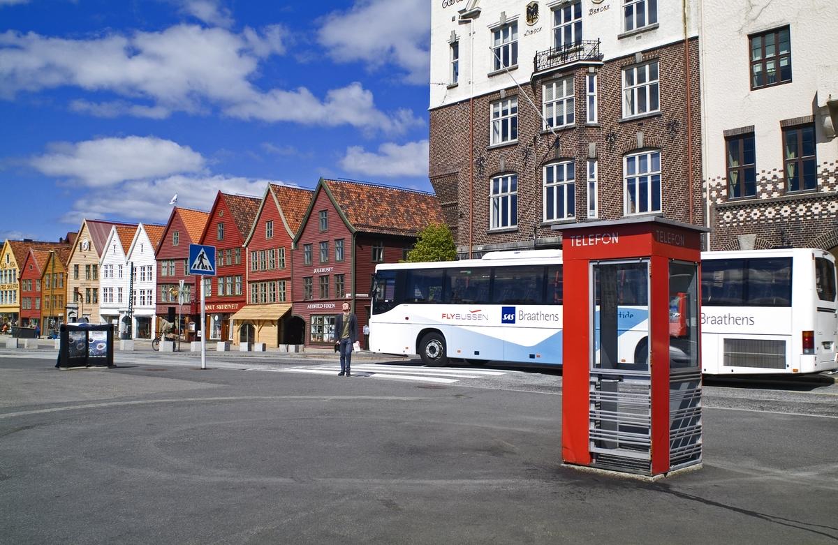 Denne telefonkiosken står på Bryggen i Bergen, og er en av de 100 vernede telefonkioskene i Norge. De røde telefonkioskene ble laget av hovedverkstedet til Telenor (Telegrafverket, Televerket). Målene er så å si uforandret.  Vi har dessverre ikke hatt kapasitet til å gjøre grundige mål av hver enkelt kiosk som er vernet.  Blant annet er vekten og høyden på døra endret fra tegningene til hovedverkstedet fra 1933. Målene fra 1933 var: Høyde 2500 mm + sokkel på ca 70 mm Grunnflate 1000x1000 mm. Vekt 850 kg. Mange av oss har minner knyttet til den lille røde bygningen. Historien om telefonkiosken er på mange måter historien om oss.  Derfor ble 100 av de røde telefonkioskene rundt om i landet vernet i 1997. Dette er en av dem.