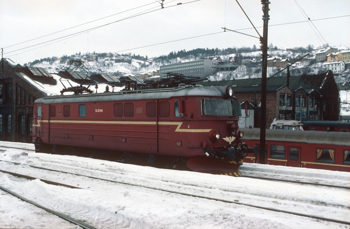 """NSB elektrisk lokomotiv El 11 2148 venter på å få kjøre inn til """"sanda"""" (sandpåfyllingen) i fjellstallen i Lodalen. I bakgrunnen sees gamlestallen."""