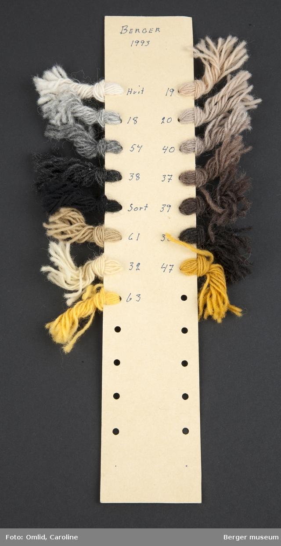 Pappremse med hull på begge sider, der garnprøver i forskjellige farger er knyttet på. Garnfargene er nummerert med blå kulepenn på kartongen.
