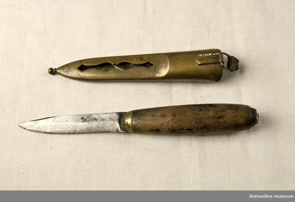 """Kniv med svartlackerat träskaft. Merparten av lackerade ytan har slitits bort. Mässingsavslutning mot knivbladet; troligen har det funnits en liknande del i skaftets ända men den saknas. Kniven har brukats. Slida av mässing, gjuten med genombruten dekor och präglat mönster. Mönsterformerna består av en krona, koslagda vapen, ett ankare samt en avlång dekorativ form. Upphängningsögla med rester av ett skinnband. """"No 13"""" stämplat på slidans överkants baksida. Både kniv och slida är märkta med tillverkarens namn.  Tillverkaren/smeden Gustaf Johan Berg, Eskilstuna, levde mellan åren 1843 - 1878.  Ur handskrivna katalogen 1957-1958: Slidkniv m. mässingslida Kniven a) L. 18,7 cm; träskaft, svart, färgen avflagnad. Slidan b) L. 14,2; krona, korsade knivar och ett ankare, delvis i genombr. arbete. Hel."""