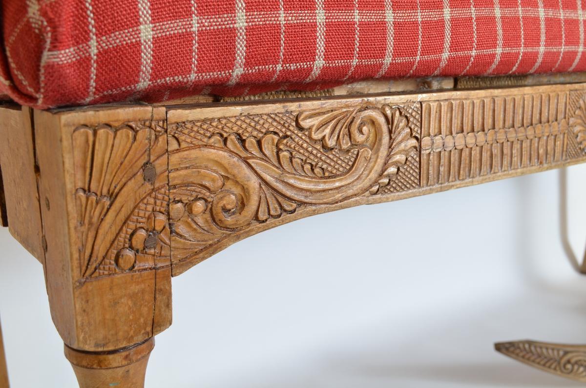 Benk i polert treverk i historisme-stil med stiliserte ranker, blomar og dekorelement. Ryggen er inndelt i tre felt med tverrgåande trestykke omlag midt i rygghøgda.   Benken har lause armlen og eit laust sete trekt i eit  raudruta tekstilmønster.