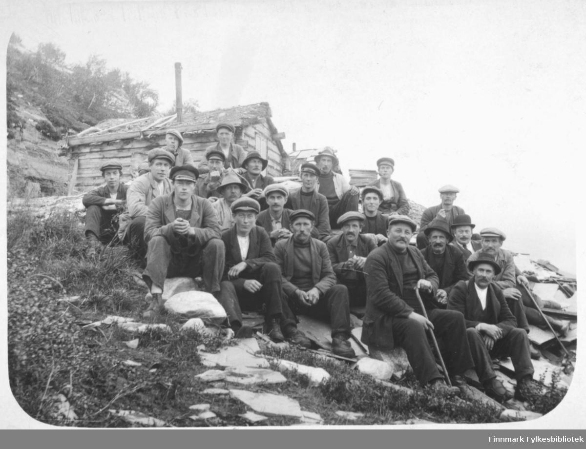 Steinberget i Alta før 2. verdenskrig. En gruppe menn av ulik alder sitter i bakken. Kristian Wisløff som ung mann ytterst til venstre. De fleste er sannsynligvis steinbergsarbeidere, sett bort fra de eldste mennene med spaserstokk. Gruppen sitter foran noen steinbergshytter. I bakgrunnen en bratt fjellside med sporadisk vegetasjon