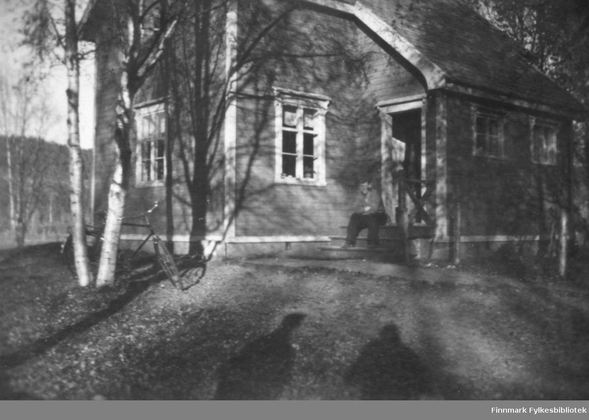 Familien Wisløffs hus før krigen. Vi ser en mann som sitter på trappa, trolig Kristian Wisløff. En sykkel står stilt opp mot noen tuntrær. Bare trær, løv på bakken og lange skygger gir bildet et høstlig preg. Ca.1930-40.