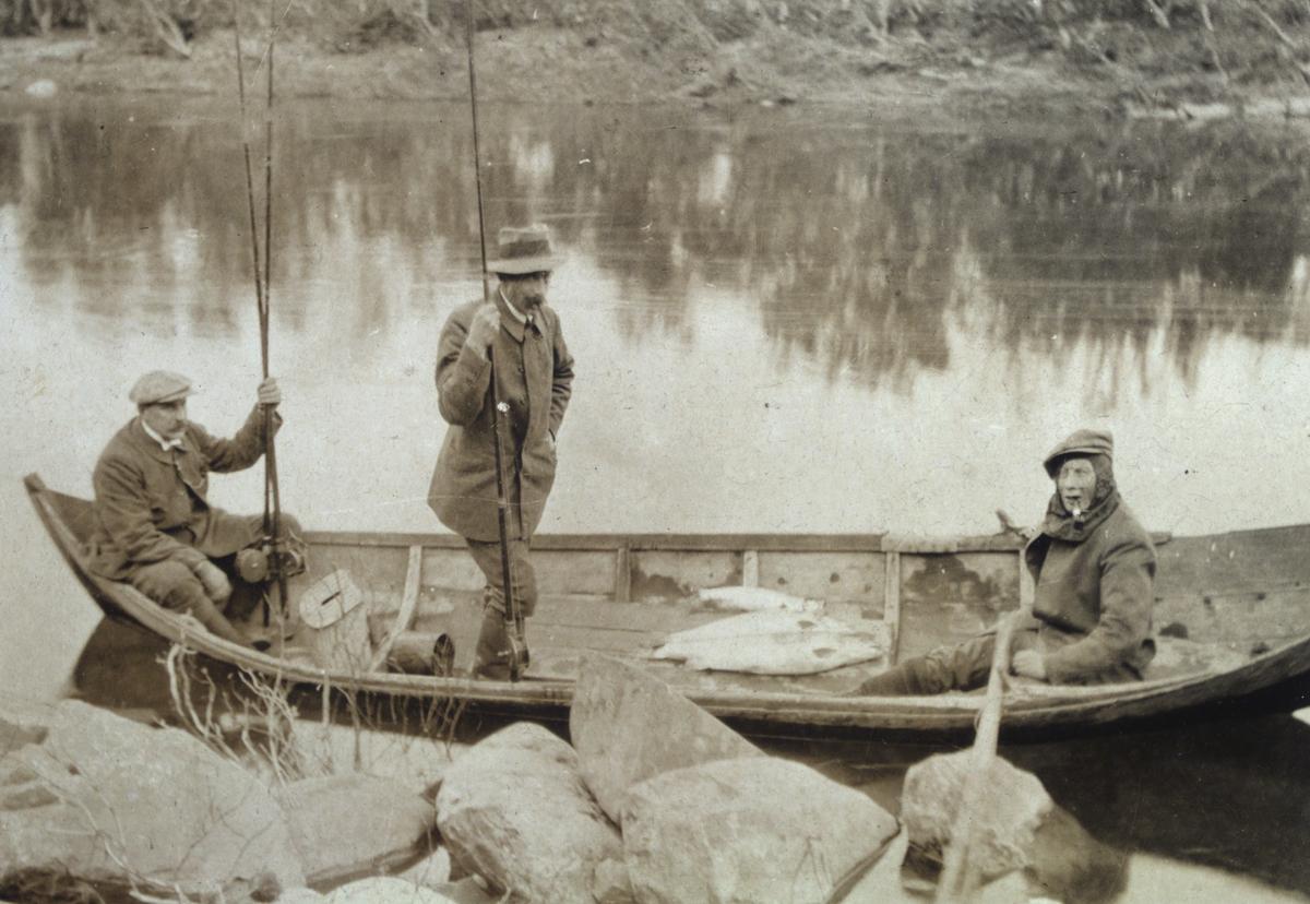 Laksefiske i Jakobselv, tre men i en elvebåt, fra venstre: Alexander Rein, Lauritz Brodtkorb og Olaf Hollum. I bunnen av båten ligger tre laks. Mennene er kledd i jakker, hatter, støvler og bukser. Ved siden av båten kan man se store steiner vid elvekanten.