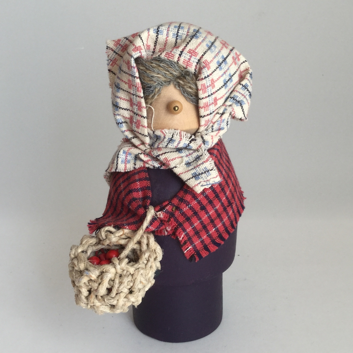 Prydnaden är en påskgumma i svarvat trä. Hon har schalett och sjal av tyg, kroppen är målad i lila.Hon bär på en korg i makramé som är fylld med små röda träkulor.Höjden är 171 mm och bredden 58 mm.