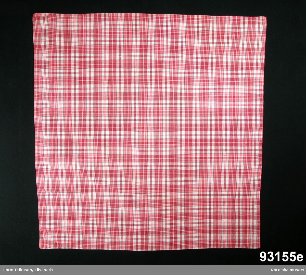 Vinterdräkt för kvinna bestående av 5 plagg, a-e. a. Röd yllekjol b. röd/grönrandig ylletröja c. rutigt förkläde av ylle d. lös halskrage e. röd/vitrutigt huvudkläde.  Huvudduk av tät och fin bomullslärft rutig i rosarött och vitt med smala handsydda fållar runtom. Berit Eldvik 2008-12-01