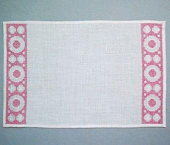 Tablett SNÖBÄR i linne broderad i korsstygn. Mönstret, i form av cirklar och ringar, är placerat som en bård i var kortsida och lämnar mittfältet tomt. Blekt/vit linneväv med broderi i rosa lingarn.