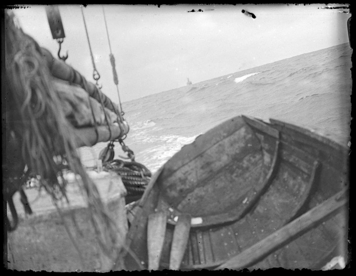 Ombord i en båt med seil. Vi ser akterenden med litt av masta. Seilet er slått ned, så båten har nok motor også. En lettbåt er dratt ombord. Sjøen ser urolig ut. En større båt akterut, er det Hurtigruta?