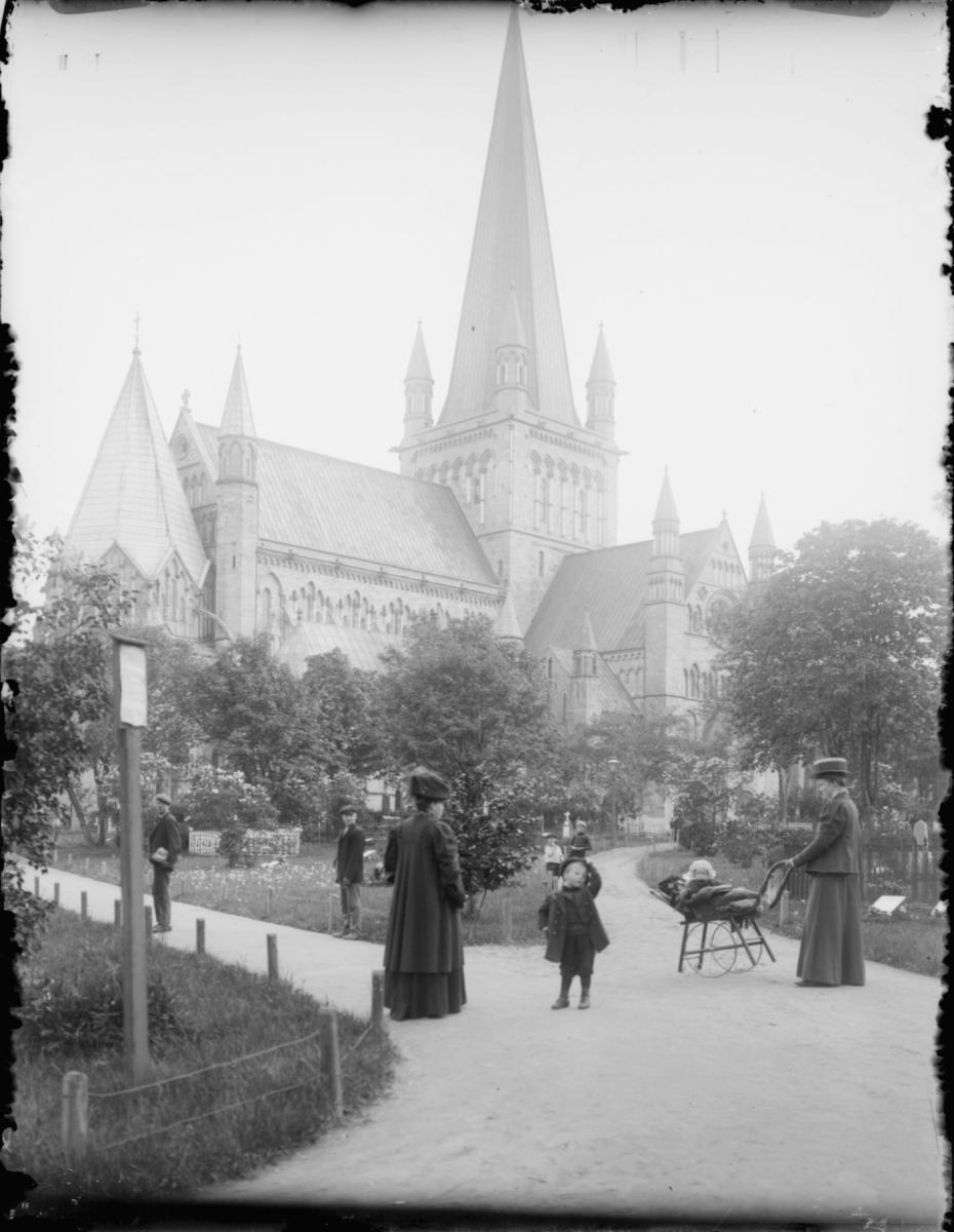 På en gravlund utenfor en kirke. To menn står til venstre. Foran står to kvinner, en med et barn i barnevogn. Tre barn til med på bildet.