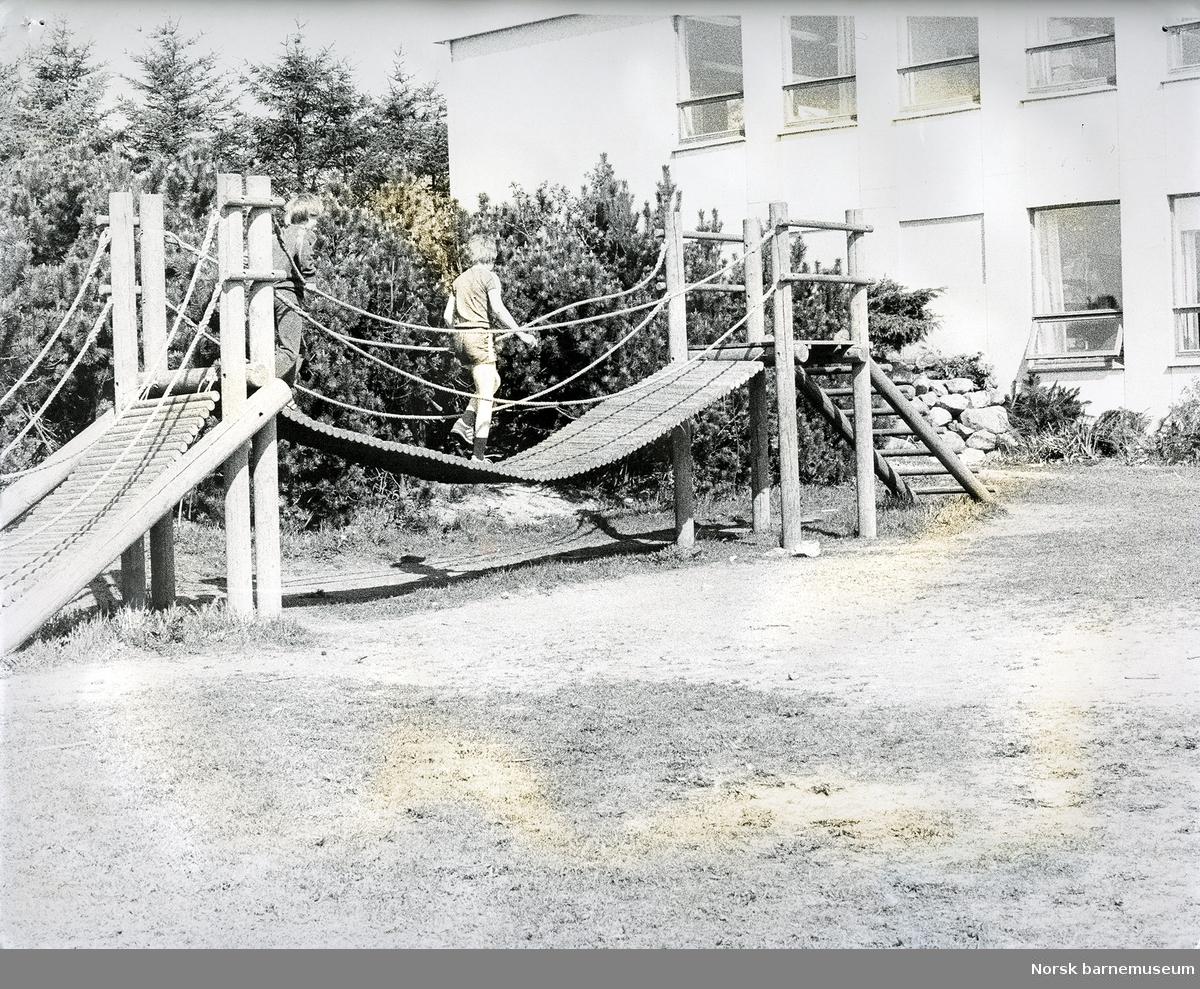 Stangeland skole med uteareal, skolegård, bro, balansestativ og en elev prøver broen.