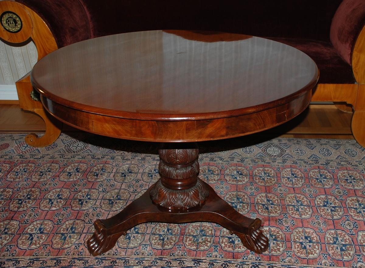 Sirkelrundt bord, polert. Rikt utskskåret søylebein, fotplate med tre utskårede dyreføtter.