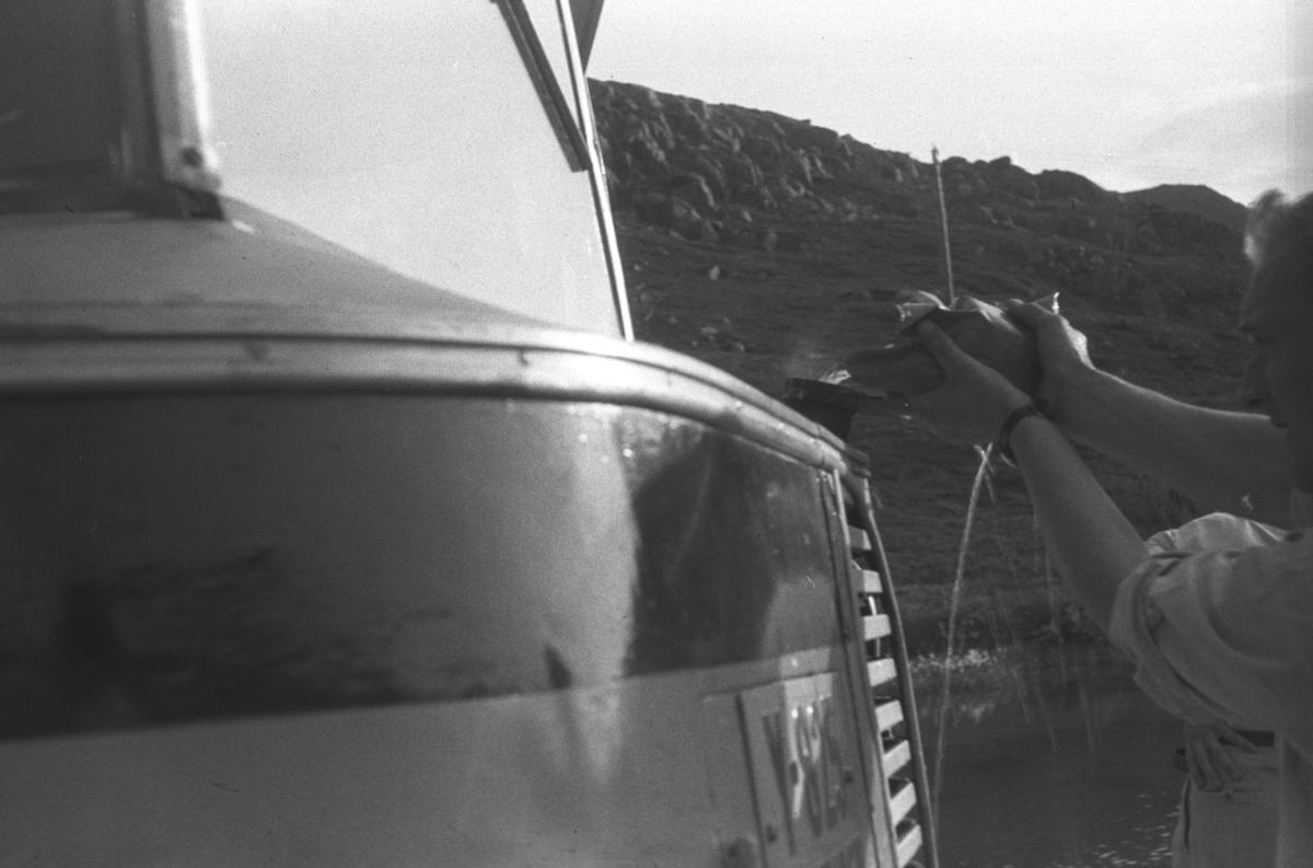 Uvisst hva dette fotografiet skal forestille, men det kan være en kvinne som fyller vann på radiatoren til en buss med registreringsnummer Y-825 som var en nummer brukt av FFR eller Finnmark Fylkesrederi og Ruteselskap. Det ble brukt først på en 1948-modell og seinere på en 1961-modell. Dette er nok 1948-modellen.