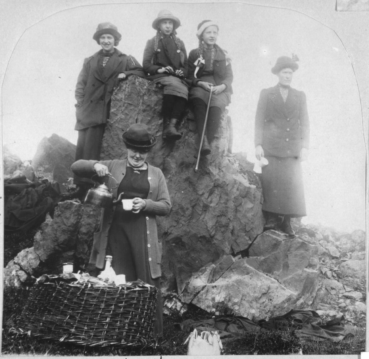 Damer og jenter som sitter og står på en stor stein. Foran står antagelig fru Ohlsen og sjenker kaffe. GForan seg en stor kurv med mat og kopper.