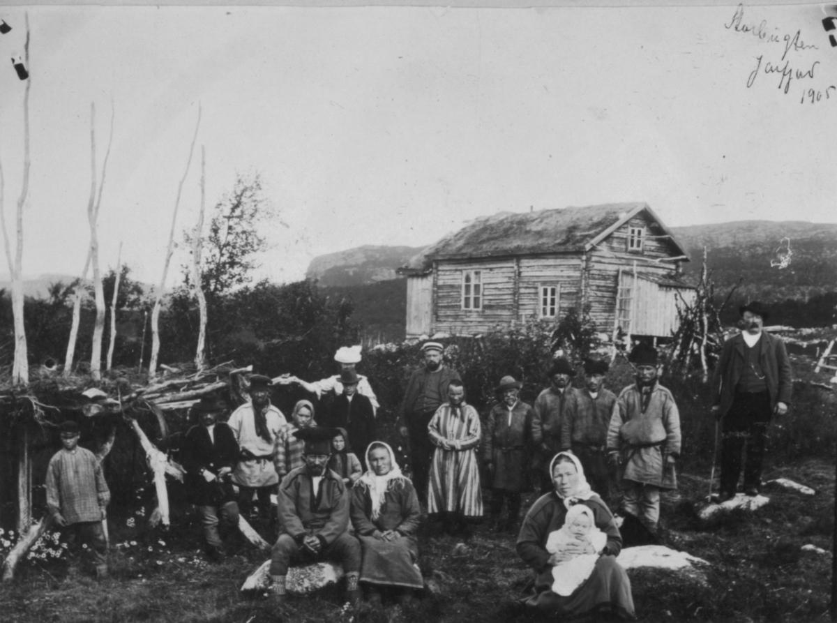 En gruppe menn go kvinne i samiske drakter fotografert i Jarfjord i 1905. Fremst på bildet en kvinne med et spedbarn i fanget. Bakerst står det et tømmerhus.