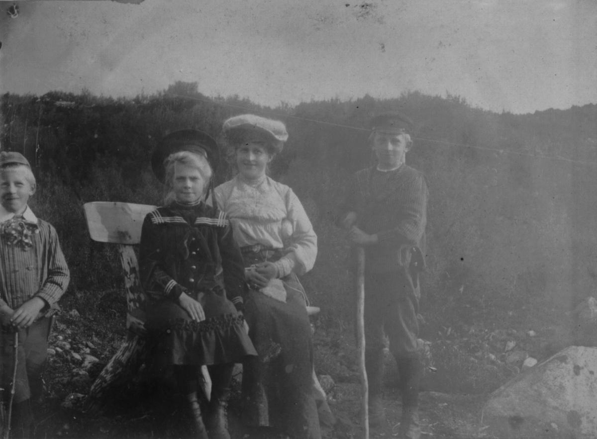 Ved Tårnelven 14. august 1907. En dame og en pike sitter på en benk. To gutter står på hver side av benken. Den ene holder en stokk i hånden.