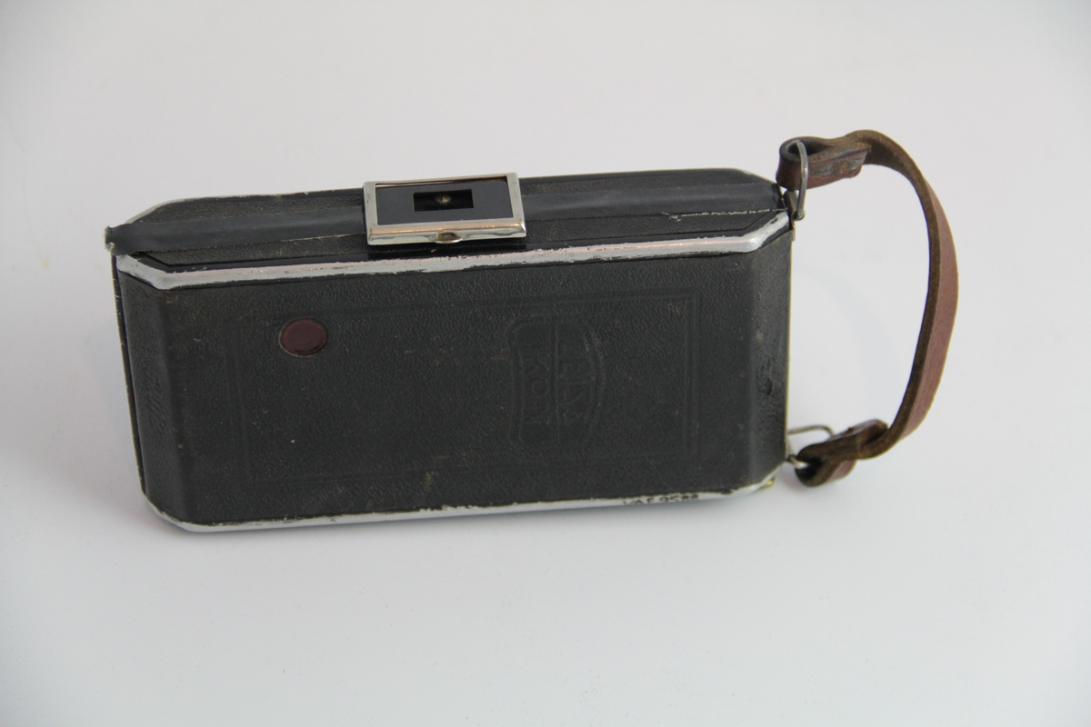 Rektangulært med avrundede kortsider. Brun lærstropp i siden. Brukt under andre verdenskrig som spionkamera.