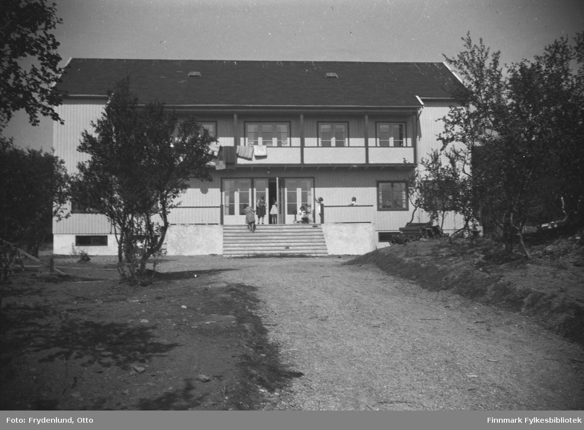 Barnehjemmet Vårsol i Vestre Jakobselv fotografert en solskinnsdag. Sommerkledte barn på trappa