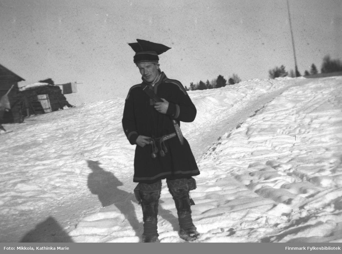 Andreas Mikkola i kofte, bellinger og med stjernelue og kniv i beltet. Bildet er tatt i Pakanajoki ca. 1946-1947. I bakgrunnen til venstre en gamme