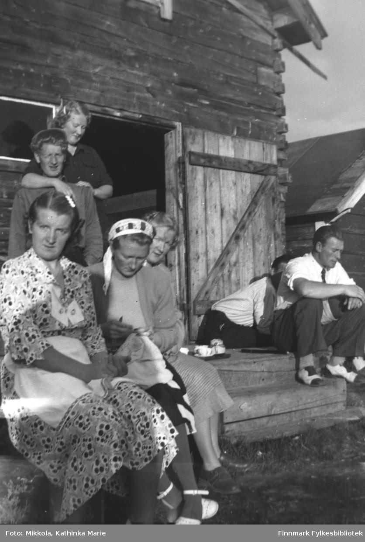 Kaffe på trammen til melkebua på Mikkelsnes, ca. 1950. Sittende, fra venstre: Astrid, Marine og Gudrun Mikkola, Sverre Olsen Lie. Marine broderer. En ukjent mann sitter med ansiktet skjult. Stående bak: Mikkel og Herlaug Mikkola