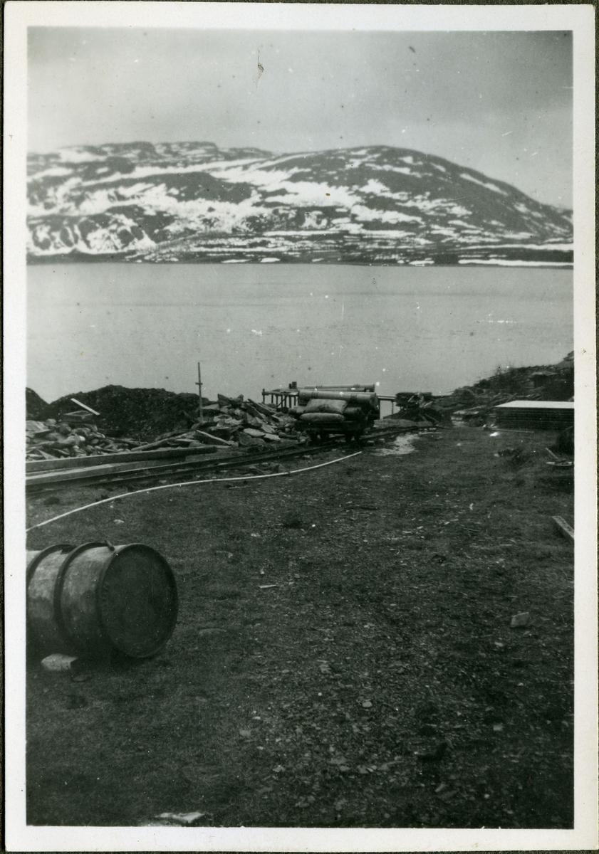 Fotografi av jernbaneskinner med vogn. Vognen er lastet med byggemateriale og hører til skiferbruddet i Friarfjord. I forgrunnen kan man se en stor tønne. I bakgrunnen ser man havet og fjell.