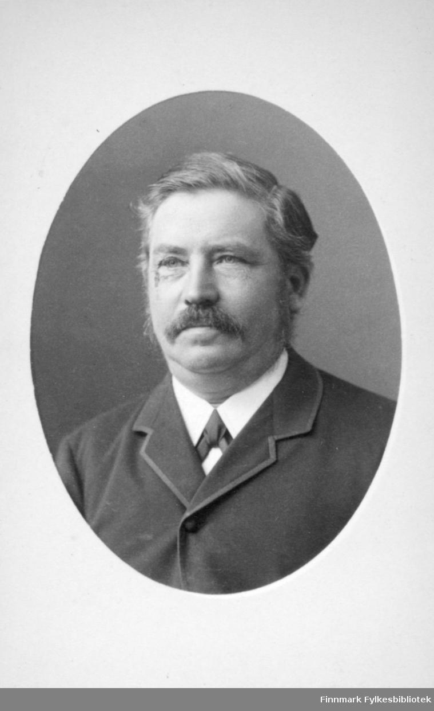 Portrett av en mann iført en mørk dress, hvit skjorte og slips eller sløyfe. Portrettet er tatt hos Frederik Klem i Christiania.