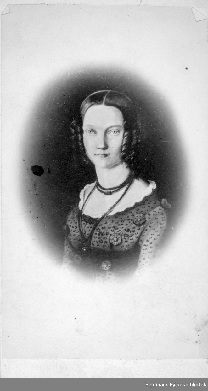 Portrett av en dame iført en mørk, tynn bluse med hvit frage. Hun har en kjede rundt halsen.