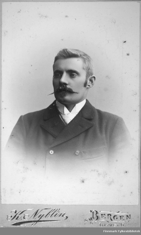 Portrett av en mann iført mørk jakke og hvit skjorte under.