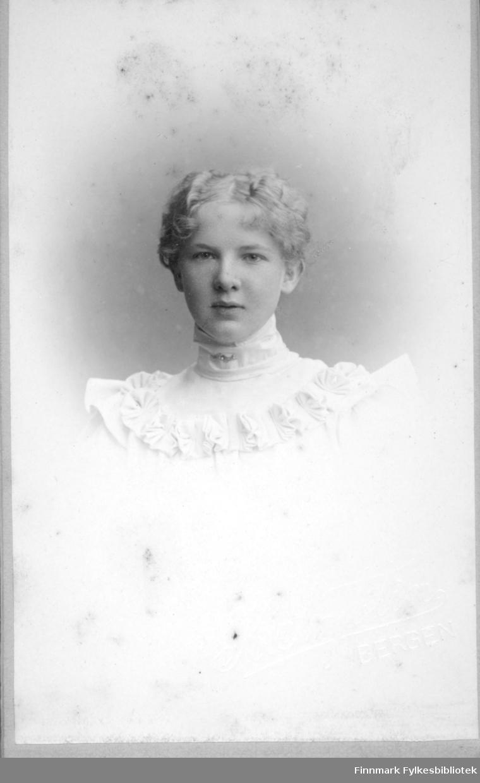 Portrett av en ung kvinne kledt i en lys eller hvit kjole med høy krage og en blondekant rundt øvre del av brystet.