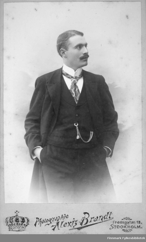 Portrett av en mann iført en mørk dress og frakk. Han har også hvit skjorte og et mønstret slips. Et lommeur-kjede henger fra vestlomma til et knappehull.