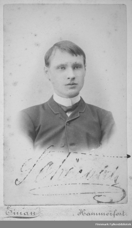 Portrett av en mann iført en mørk dressjakke. Han har en hvit skjorte med kragen oppbrettet. En sløyfe eller slips er knytt rundt halsen.