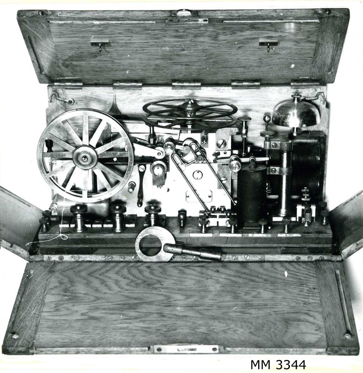 Telegrafapparat av metall, förvarad i låda av trä.