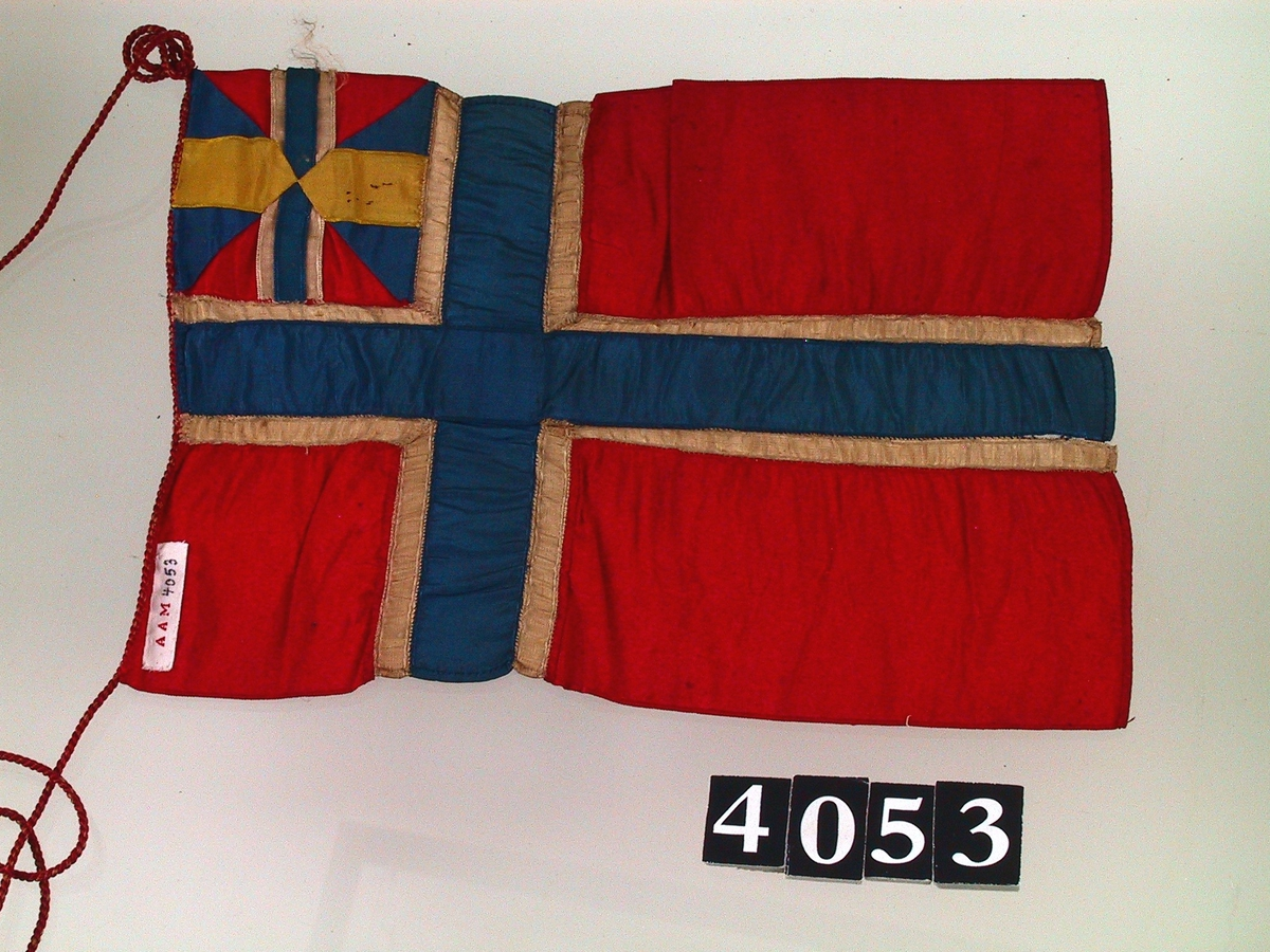 Håndsydd  flagg med unionsmerke. Lang tynn snor påsydd, av lys brun bomull  stråd omviklet med dyprød silketråd.  Tilstand jan. 1965: krøllet, skittent. Rengjort.