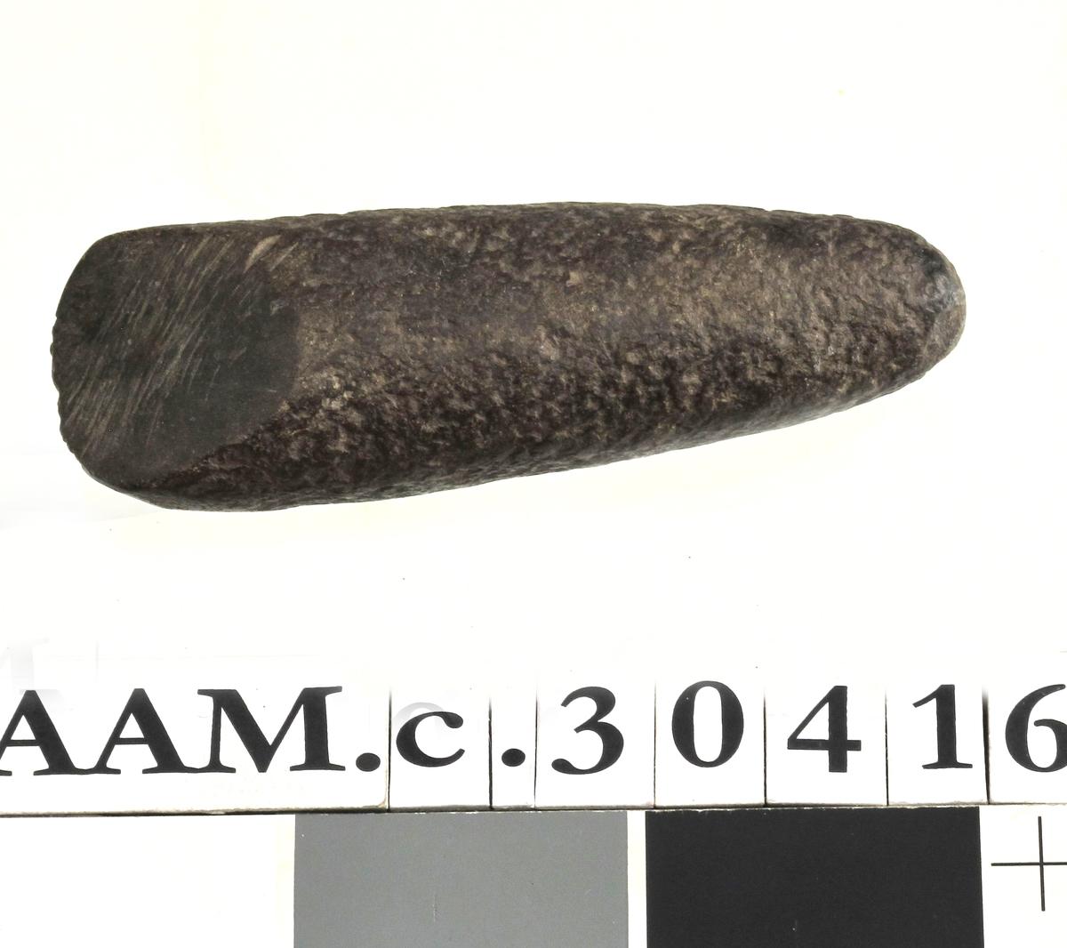 Buttnakket trinnøks av svart, tett bergart av typen [Rygh fig.12]R. 12. Oversiden delvis slipt. Her er dessuten en kort tverregg slipt til (sekundært). På den ene siden merket KK (Knud Knudsen) som var finneren. Godt bevart. Lengde 11,4 cm, breddeover eggen 3,7 cm.