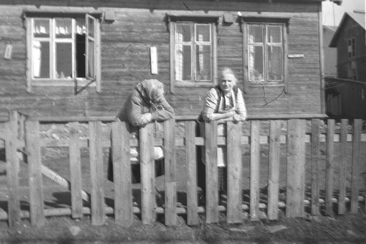 To damer står ved et gjerde en solskinnsdag i Vadsø. Damen til venstre på bildet heter Lydia, etternavnet er uskikkert, men hun var født Keskitalo. Ved siden av henne står Astrid Ballo.