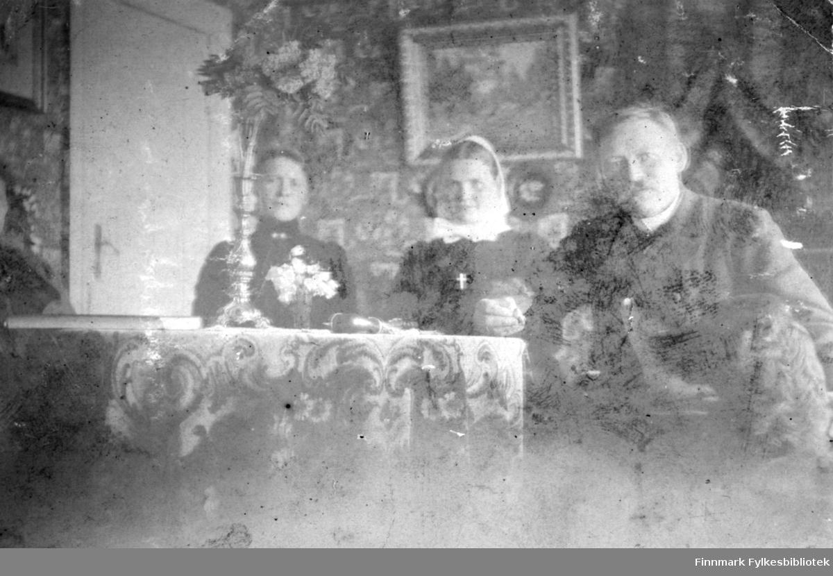 En mann og to kvinner sitter ved et rundt stuebord. Oppå bordet ligger en mønstret du. Mannen har dressjakke med hvit skjorte. Damene har mørke overdeler og hun i midten har en lys krave og et lyst hårband. Bak dem henger et maleri på den mønstrete veggen. En dør står til venstre og på bordet står to blomstervaser, begge med blomster i.