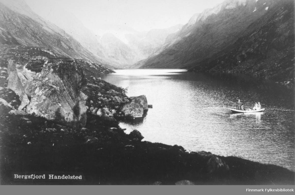 En robåt med fire personer fotografert oppe ved Dalvannet, tilhørende Bergsfjord, Loppa. I bakgrunnen sees isbreen, Øksfjordjøkelen.