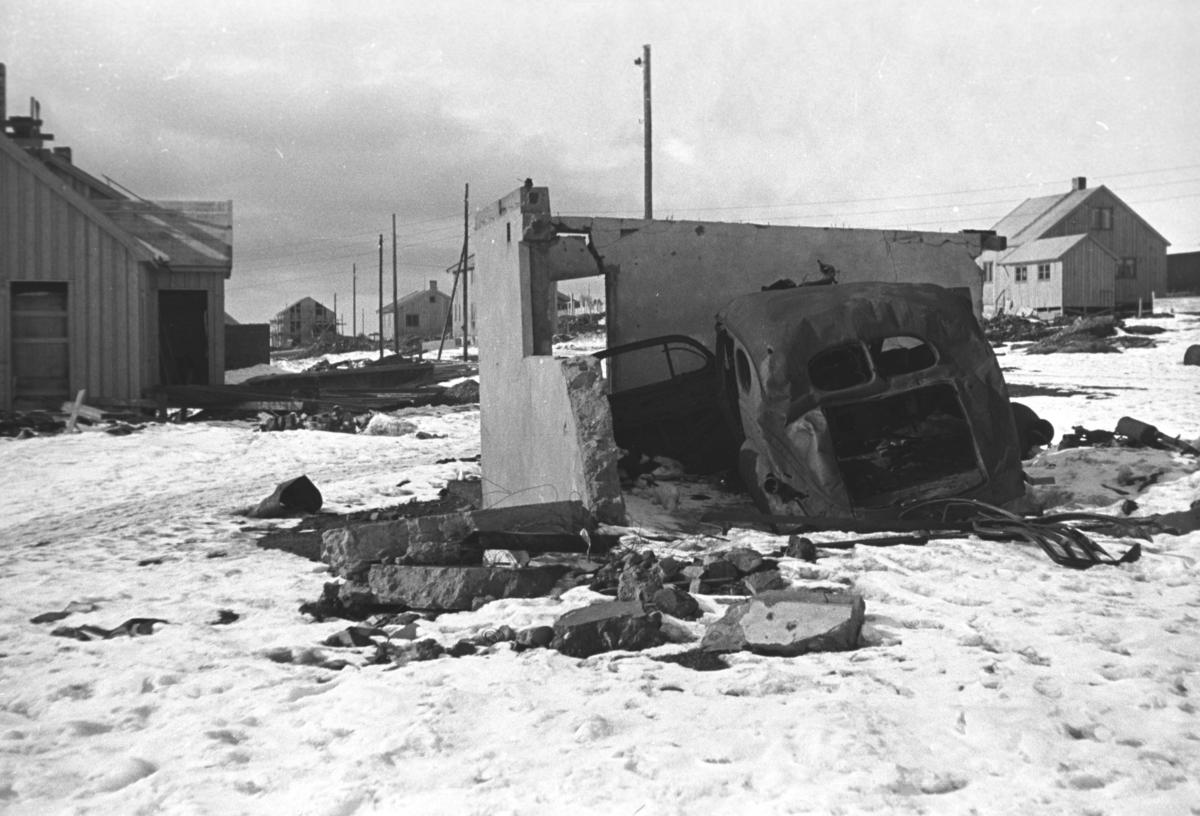 Et bilvrak står ved en delvis rasert garasje i nærheten av Vadsø skole.