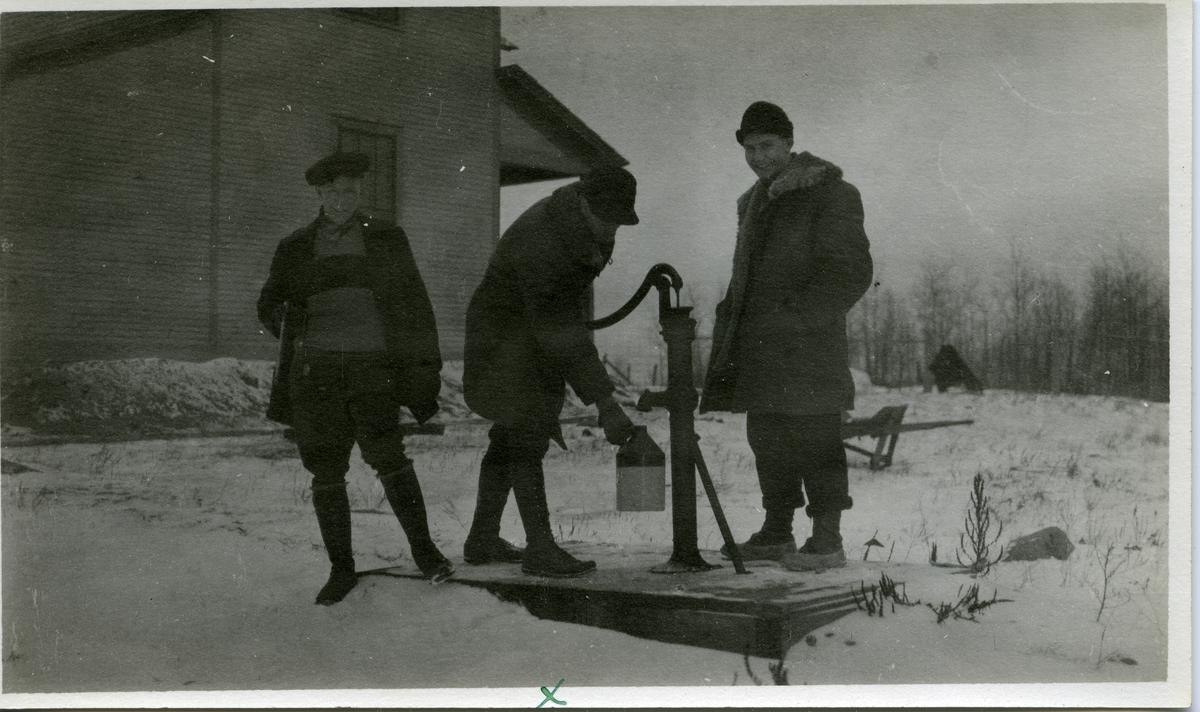 Tre menn avbildet foran en vannpumpe. Mennene er iført vinterklær og en av mennene pumper vann. Bildet er tatt i forbindelse med en harejakt.