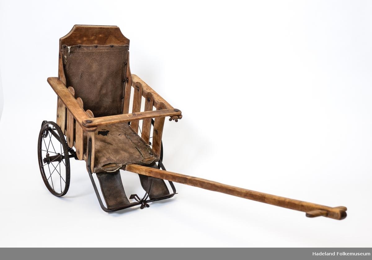 Sittevogn for småbarn. Fjæring på bærende hjulgang. Stopping i sete og rygg, trukket med plastbelagt, brunt lerret. Med unntak av hjul og hjulgang er trillen laget i treverk, trolig løvtre. Hjulene har vært gummibelagt. To mindre støttehjul i støpejern bak som hindrer trillen i å tippe.  Ikke regulerbart sete eller fotstøtte. En trekk-arm som kan reguleres i høyden.