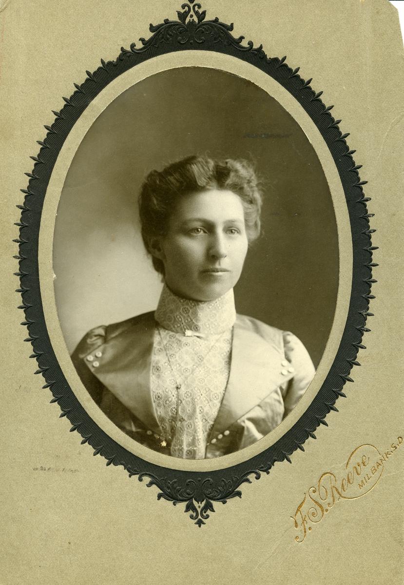 Portrett i halvfigur av kvinne. Blondebluse og silkejakke.