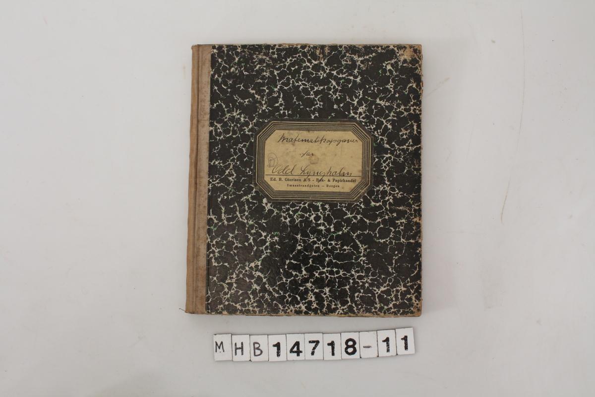 Kladdebok med matematikkoppgaver, skrevet av Odd Lyngholm. Spettede grønt, sort og hvitt papir på boksomslaget. Håndskrevende notater.