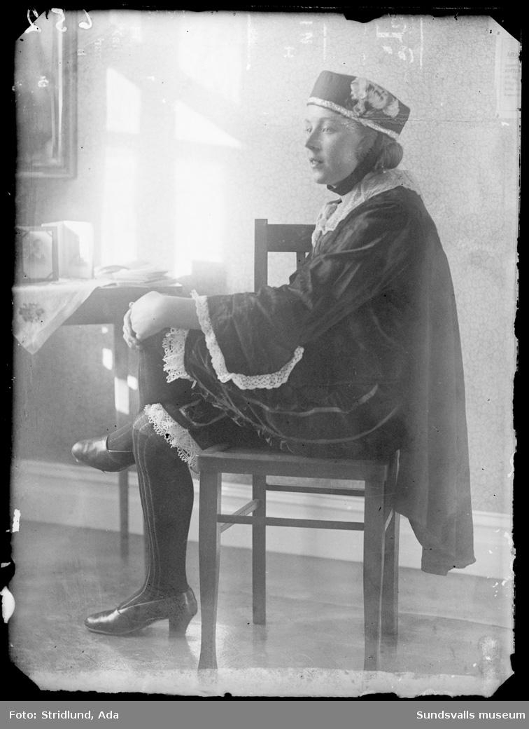 Okänd kvinna med speciell klädedräkt sittande på stol i ateljé.