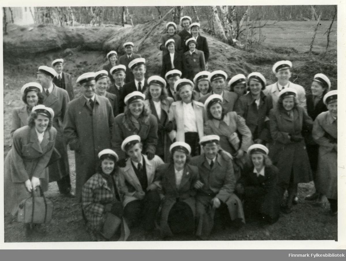 Bildet er tatt i Tana 19.juni 1949. Avbildet er medlemmer av Vadsø damekor og mannskor. På seg har alle hvite hatter, som trolig er kor uniform. Mange av kvinnene har på seg kåper og skjørt. Mennene har på seg jakker, vester og slips. Første rekke sitter på bakken. Mannen i andre rekke nr.2 fra venstre har på seg briller.