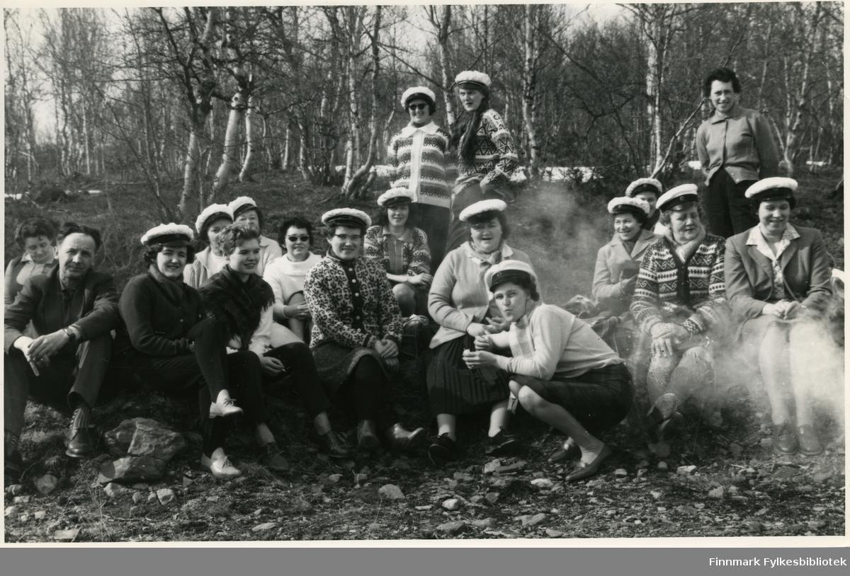 Vadsø damekor tar en pause på bussturen til sangerkorstevnet i Berlevåg 1962. Identitetene til noen av personene i bildet er noe usikkert. Første rekke sittende fra venstre: Rolf Bohinen, Selma Thomasen, Edel Berg, Ingrid Niskavara, Aslaug Aronsen, Mary Bohinen (på kne), Lissi Esbensen og Turid Bjørkli. Bakerste rekke fra venstre: fru Moxnes, Aslaug/Astrid Karlsen (?), Alfhild Bohinen (?) (bak Edel Berg), Mimmi Zahl (mellom Edel og Ingrid Niskavara), resten i rekken ukjent. Stående bakerste rad fra venstre: Margith Krogh, Solveig Berge og helt til høyre, Liv Bjørgan Pedersen. Mange av kvinnene har på seg hvite hatter. De har på seg gensere, jakker, kåper og skjorter. De fleste har på seg skjørt. Damene drikker fra kopper og spiser mat. I bakgrunnen kan man se trær og på bakken ser man steiner.
