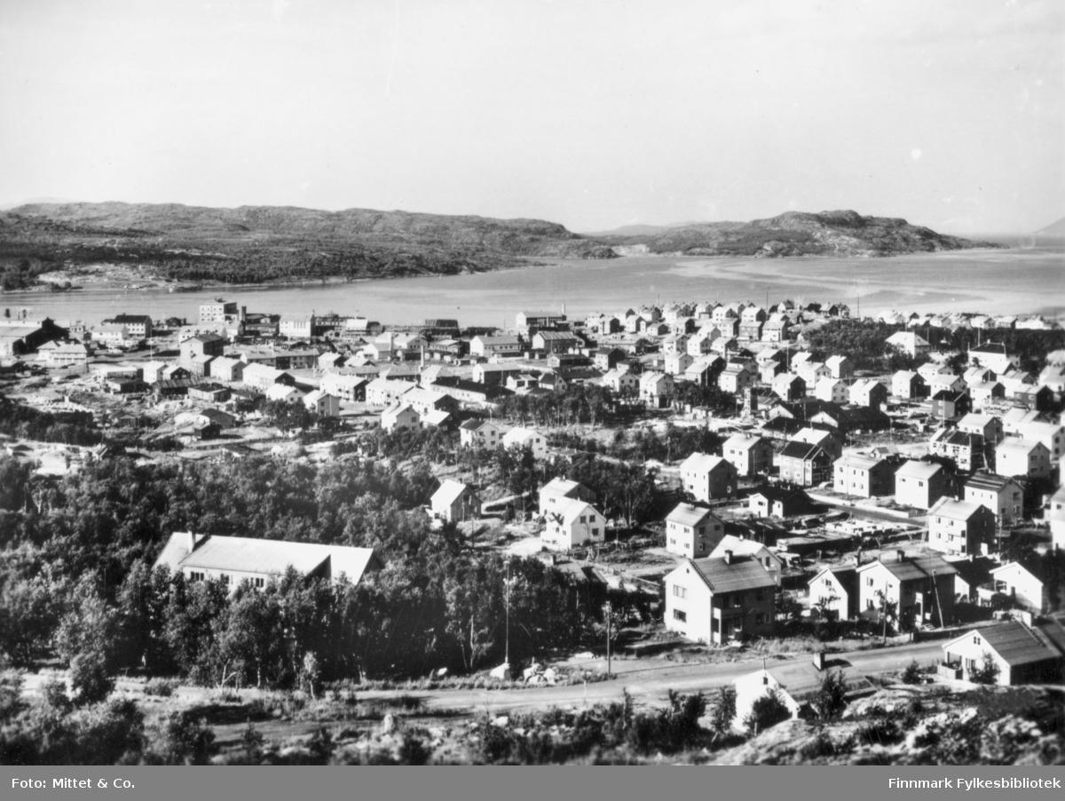 Et bybilde av Kirkenes. I byen kan man se flere hus og gater. I bakgrunnen kan man se fjell og havet.