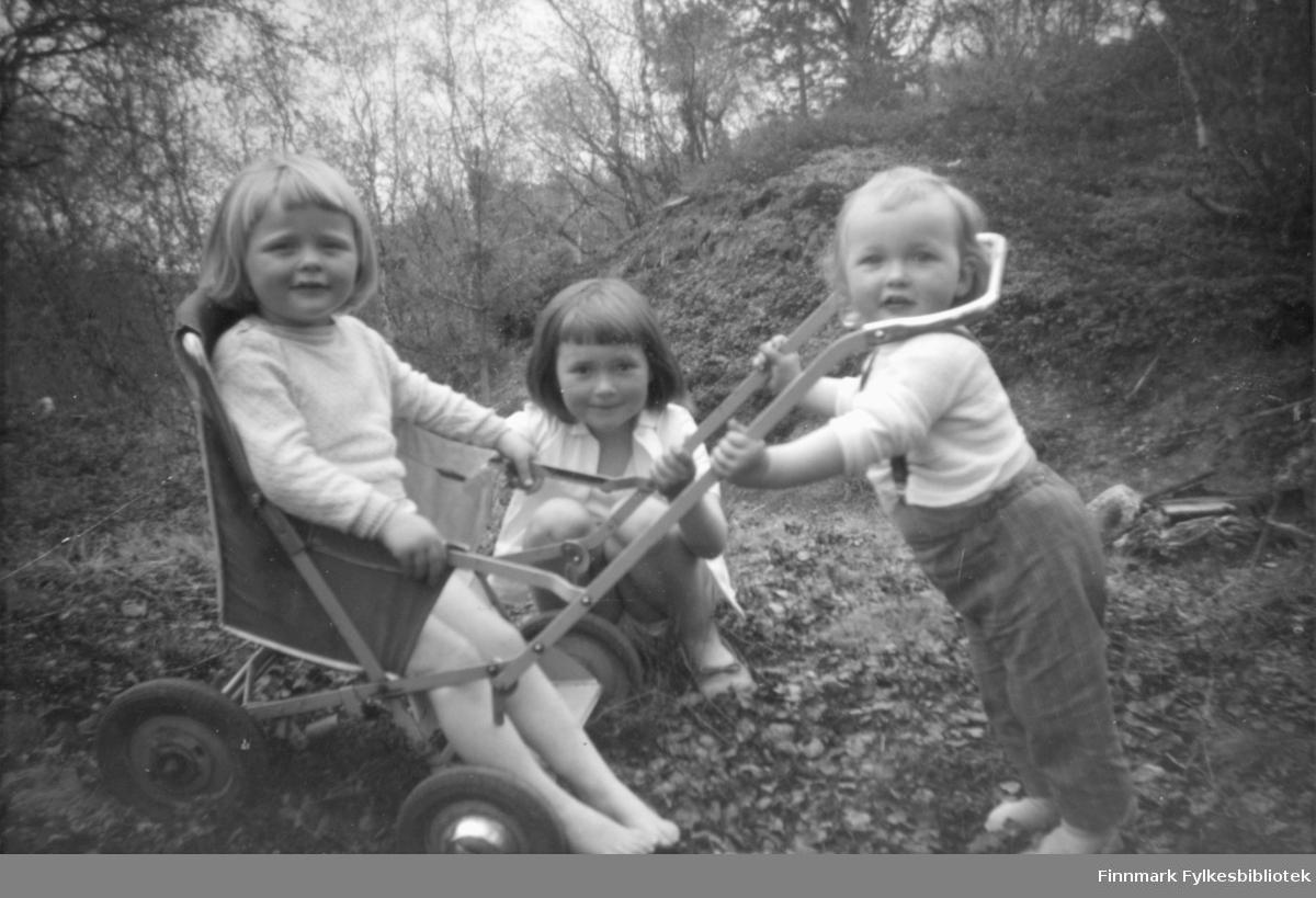 Tre søstre som leker med en barnevogn, type sportsvogn. Fra venstre, Inger Jakobsen som sitter i vogna, Torunn Jakobsen g. Mathisen på huk, og Elisabeth Jakobsen g. Ring som står. De er i et område med trær omkring
