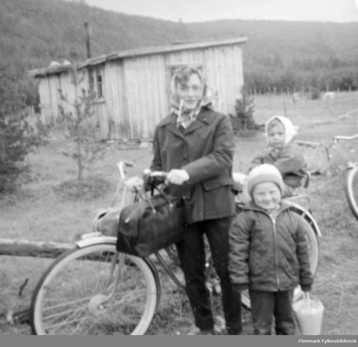 På vei hjem etter besøk på Gammelsetra. Anna Elisabeth Uglebakken f. Johansen med barna Torill og Trond Einar. De har en sykkel som fremkomstmiddel. På sykkelstyret henger det vesker. Trond Einar holder en bøtte i hånden. Torill sitter i et barnesete bakpå sykkelen. I bakgrunnen ser vi seterstua. Den var en trebrakke som bestod av to små rom. Setra lå øverst oppe i Tverrelvdalen under fjellet Nalganas. Det er trær omkring