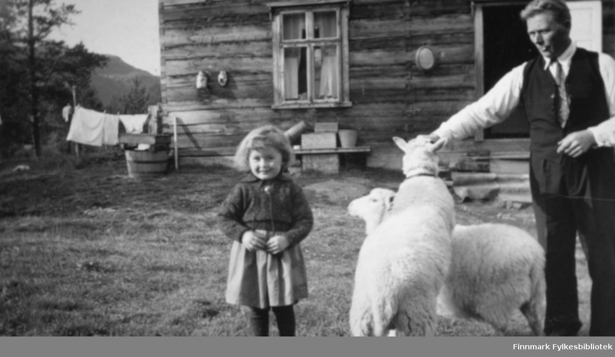 Karen Kristine Jakobsen f. Johansen, og pappa Andreas Julius Johansen foran huset på Fjellstad. Det er to hvite sauer sammen med dem. Det henger tøy til tørk ved siden av huset. På hjørnet står det en trestamp. Døren inn til huset står åpen. Andreas er kledt i mørk bukse og vest. Han har hvit skjorte og slips i halsen. I munnen har han en tobakksrøyk. Karen Kristine har på seg genser og skjørt. Fjellstad lå øverst oppe i Tverrelvdalen, og ble bygd i 1927 av Andreas Julius. I 1940 ble gården solgt til Fredrik Hapalahti. Da flyttet familien Johansen ned til Gamnes