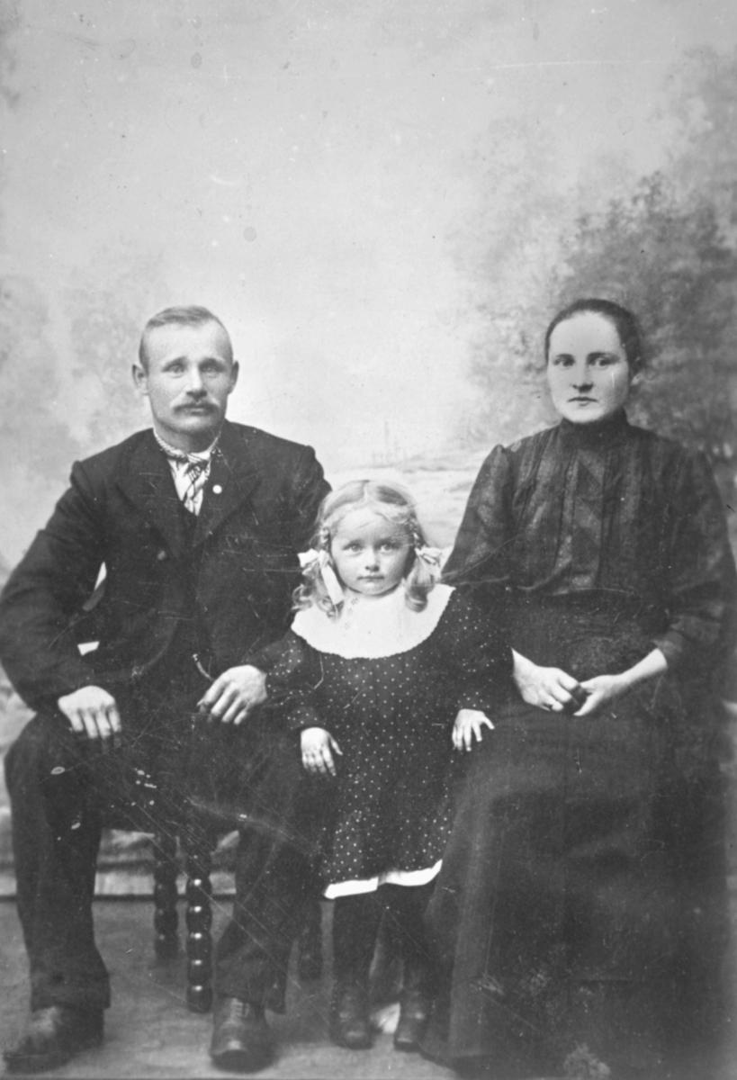 Familie fotografert hos Emilie Henriksen. Far Oskar Ittelin sitter på stolen som har dragehoder på armlenene, mor Emma sitter ved sidan av han og datteren Julie står mellom dem. Alle har er finekledde. På bakgrunn malt landskap.