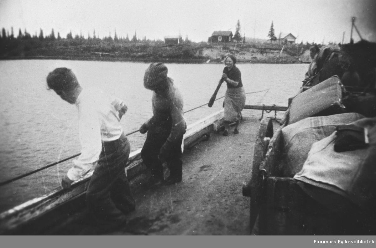 En kvinne og to menn drar ei ferge over en elv i Petsamo / Petsjenga
